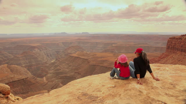WS Rear view of woman and girl (6-7) sitting on edge of canyon enjoying views / Muley Point, Utah, USA