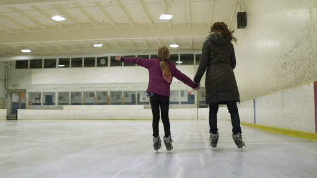 rear view of woman and young girl on ice rink ice skating together holding hands. - ice skating stock videos & royalty-free footage