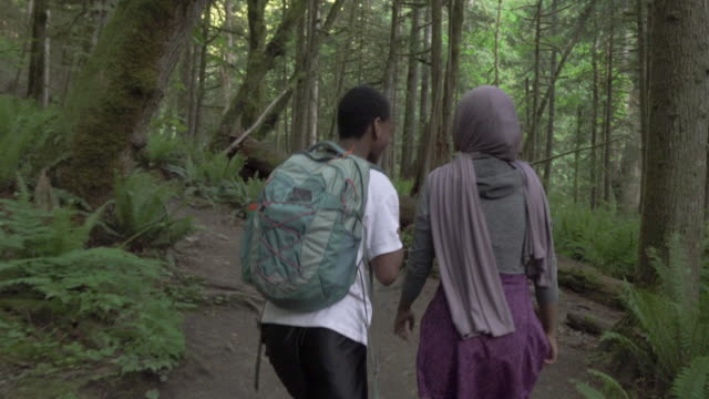 vidéos et rushes de rear view of woman and young man hiking on summer evening - vêtement religieux