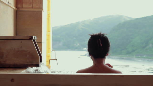 slo mo cu rear view of woman bathing in traditional hot spring (onsen), green hills in background / izu, japan - varm källa bildbanksvideor och videomaterial från bakom kulisserna
