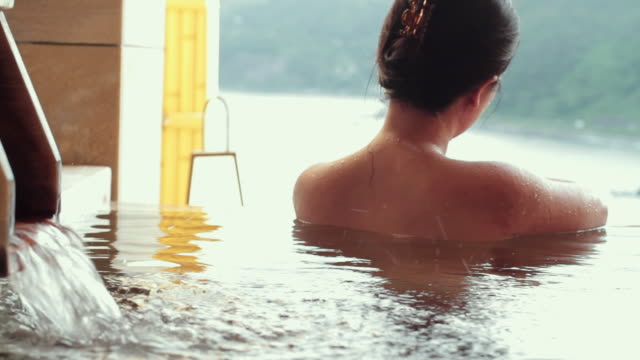 slo mo cu rear view of woman bathing in traditional hot spring (onsen) / izu, japan - varm källa bildbanksvideor och videomaterial från bakom kulisserna