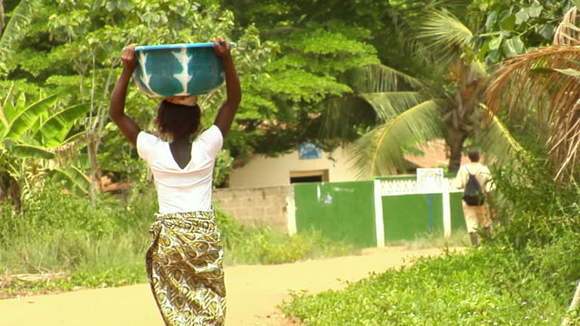 WS, Rear view of woman carrying vessel with water on head towards village, Bonou, Porto-Novo, Benin