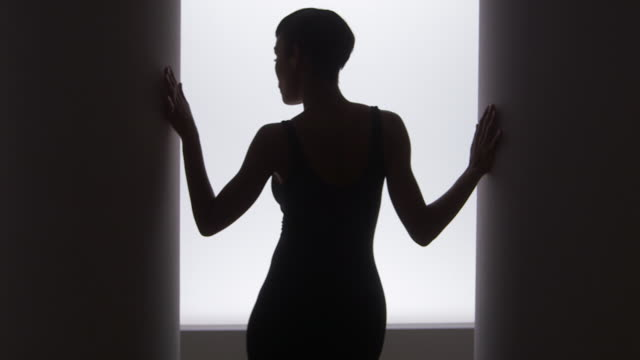 rear view of woman dancing in front of bright light - ballet dancer stock videos & royalty-free footage