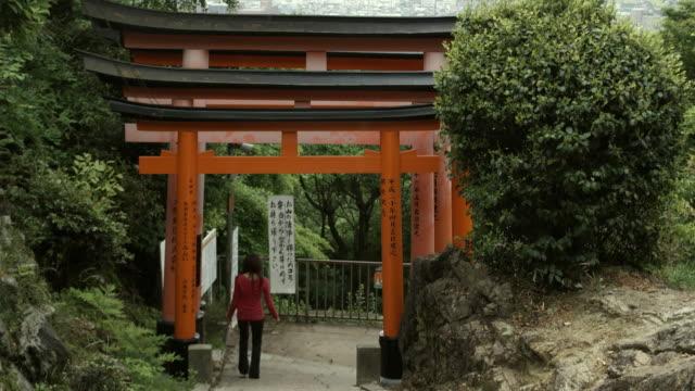 WS TU Rear view of woman descending steps under Torii gates at Fushimi Inari Taisha shrine and cityscape, Kyoto, Japan