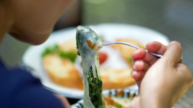 rear view of woman eating baked spinach with cheese on the table with many food in background - lasagna stock videos & royalty-free footage