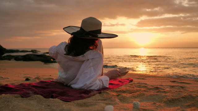 rear view of woman in straw hat and shirt reading book on beach at sunset - asciugamano video stock e b–roll