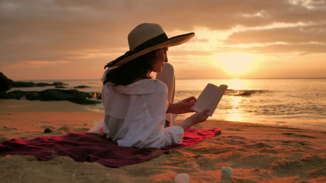 vídeos de stock e filmes b-roll de rear view of woman in straw hat and shirt reading book on beach at sunset - toalha