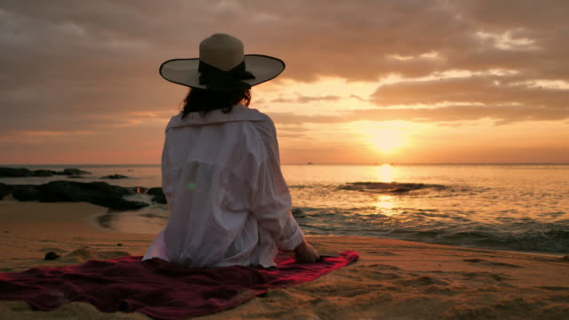 rear view of woman in straw hat and shirt reading book on beach at sunset - tied bow stock videos & royalty-free footage