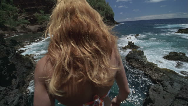 vidéos et rushes de slo mo, ws, ha, rear view of woman jumping from cliff, maui, hawaii, usa - cliff
