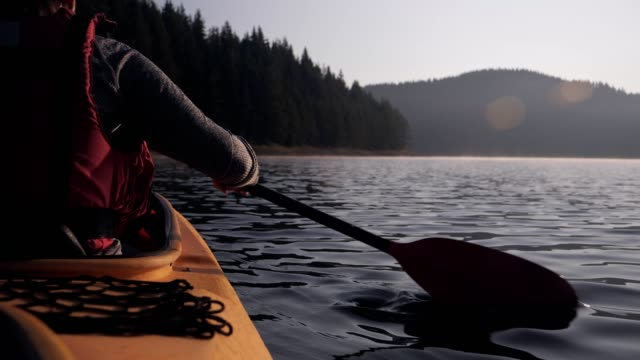 rear view of woman kayaking - remo video stock e b–roll