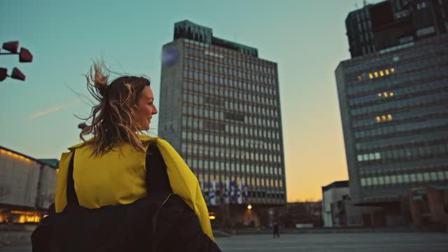 vidéos et rushes de vue arrière d'une femme regardant les bâtiments modernes de la rue de la ville - regarder autour de soi