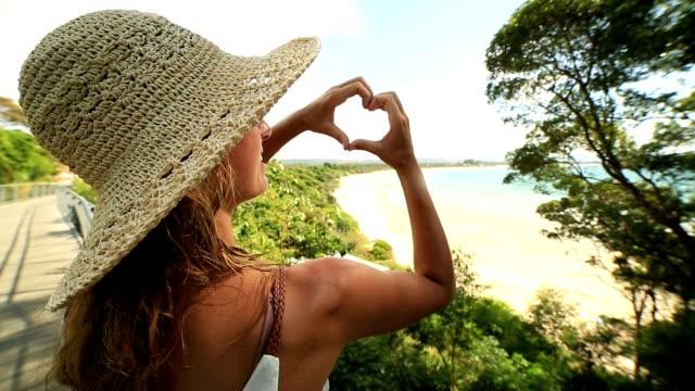 Rear view of woman making heart shape frame on beach