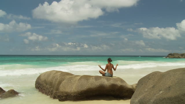 ws rear view of woman meditating on boulder on beach / seychelles - entspannungsübung stock-videos und b-roll-filmmaterial