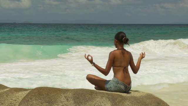 vídeos y material grabado en eventos de stock de ws rear view of woman meditating on boulder on beach / seychelles - brazo humano