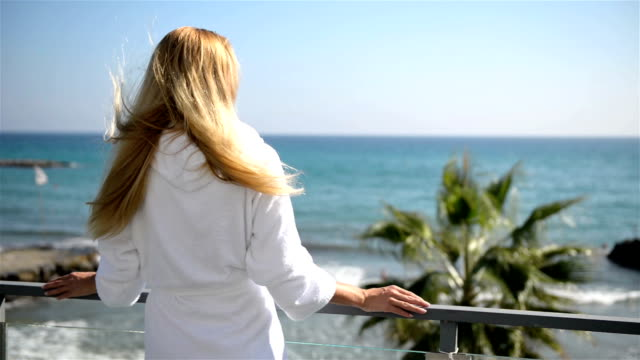 Rear view of woman on a balcony with sea view