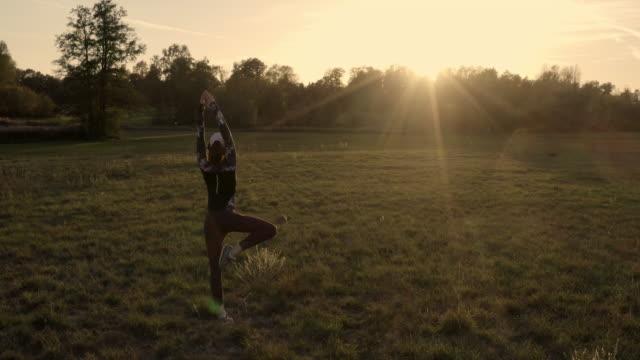 rear view of woman performing yoga in green field at sunset - auf einem bein stock-videos und b-roll-filmmaterial