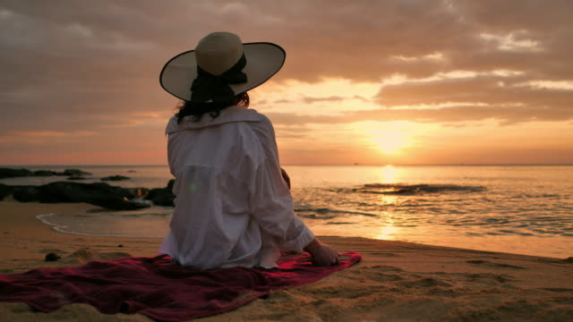 rear view of woman relaxing on beach at sunset - lying on back stock videos & royalty-free footage