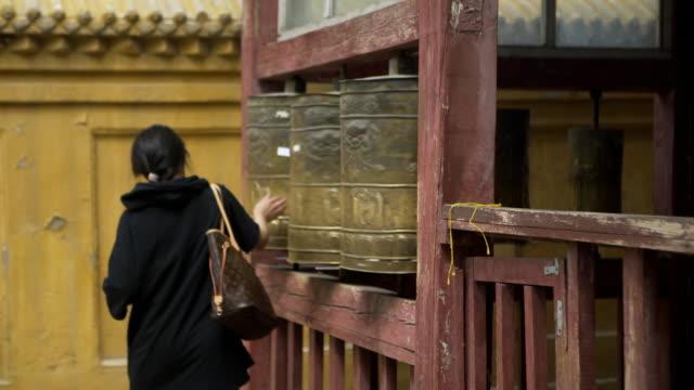 rear view of woman rolling prayer wheel at buddhist temple - ulaanbaatar, mongolia - ulan bator stock videos & royalty-free footage
