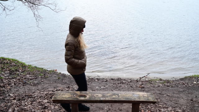 rear view of woman sitting on a wooden bank in the small beach of a lake in a winter day. germany. brandenburg. - ウィンターコート点の映像素材/bロール