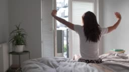 Rear view of woman stretching in bedroom