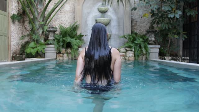 vídeos y material grabado en eventos de stock de rear view of woman submerging herself in pool. - mérida méxico