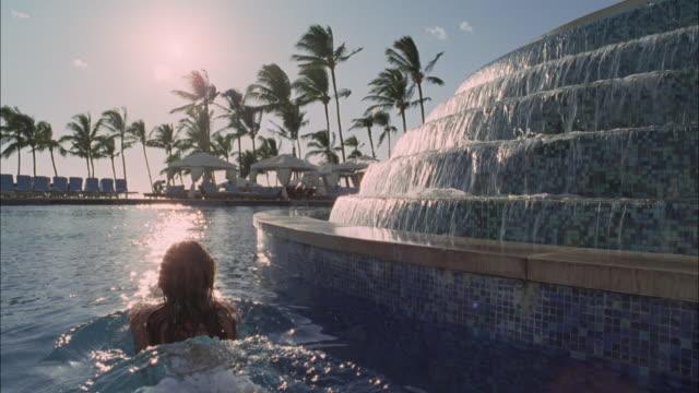 vídeos de stock, filmes e b-roll de cu, rear view of woman swimming in pool in luxurious resort, maui, hawaii, usa - fan palm tree