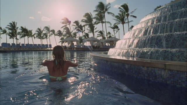 CU, Rear view of woman swimming in pool in luxurious resort, Maui, Hawaii, USA