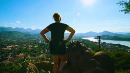 Rear View of Woman Tourist Looking at and Landscape and Skyline Cityscape View on Sunny Day in Luang Prabang, Laos