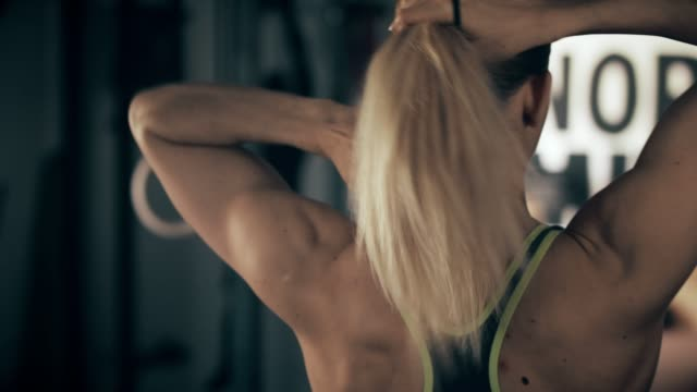 rear view of woman tying hair in gym - coda di cavallo video stock e b–roll