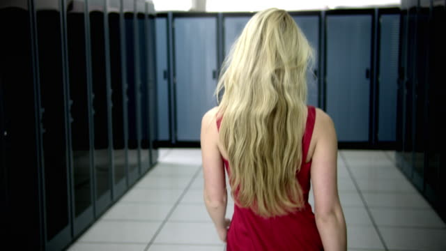 CU DS Rear view of woman walking in server room, turning and looking to camera