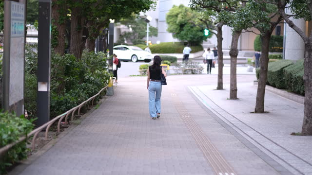 rear view of woman walking on street - one mid adult woman only stock videos & royalty-free footage