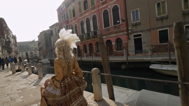 rear view of woman wearing historical clothing and carnival mask walking by canal - historical clothing stock videos & royalty-free footage