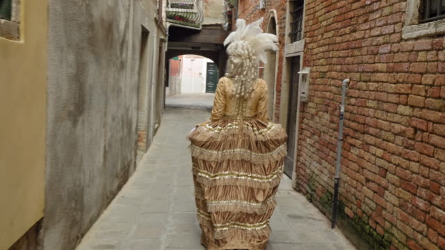 rear view of woman wearing historical clothing walking in narrow alley - historical clothing stock videos & royalty-free footage