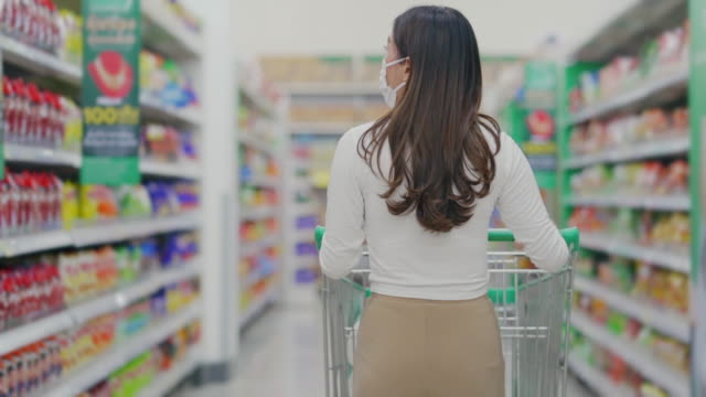rear view of woman with shopping cart in supermarket - spuntino video stock e b–roll