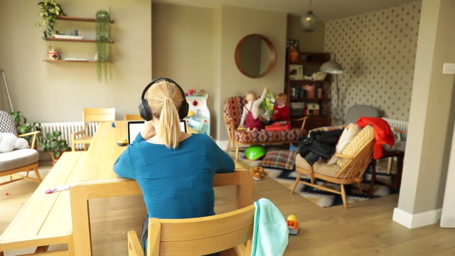 rear view of woman working on laptop at table while children playing on sofa amid coronavirus pandemic in guildford, surrey, uk on friday, september... - berufstätige mutter stock-videos und b-roll-filmmaterial