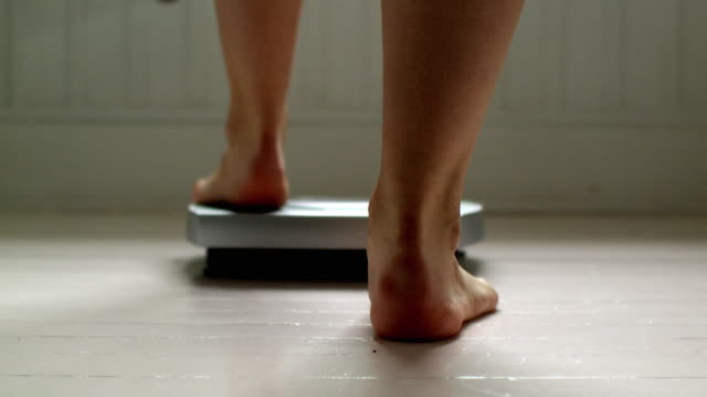 CU Rear view of woman's feet on bathroom scale, Scarborough, New York, USA