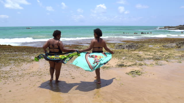 rear view of women sunbathing on tropical beach - uv protection stock videos and b-roll footage