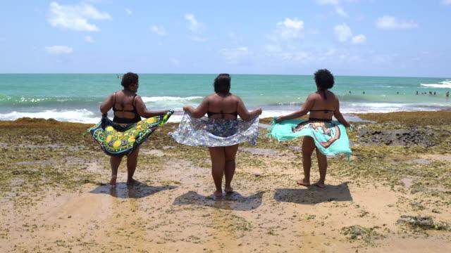 rückansicht der frauen beim sonnenbaden am tropischen strand - dicke frauen am strand stock-videos und b-roll-filmmaterial