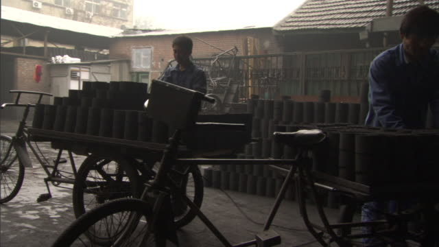 ms pan ws rear view of worker riding tricycle with charcoal bricks from factory, beijing, china - tricycle stock videos & royalty-free footage
