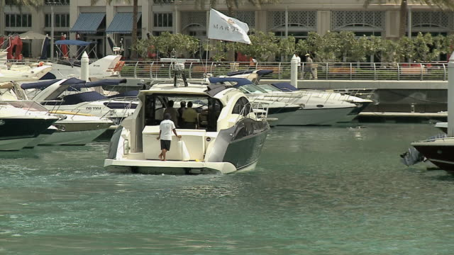 ws rear view of yacht traveling through dubai marina / dubai, united arab emirates - motorboat stock videos and b-roll footage