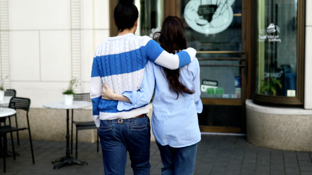 Rear View Of Young Couple Entering Cafe