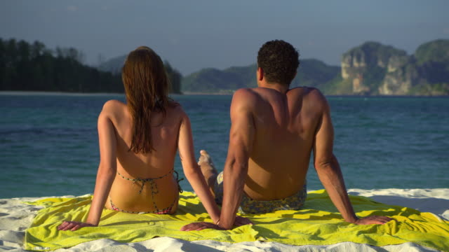 stockvideo's en b-roll-footage met ms pan rear view of young couple facing sea on tropical beach, krabi, thailand - zwembroek