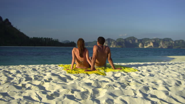 stockvideo's en b-roll-footage met ws pan rear view of young couple facing sea on tropical beach, krabi, thailand - zwembroek