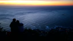 Rear view of young couple on top of lion's head looking at sunset HD VIDEO