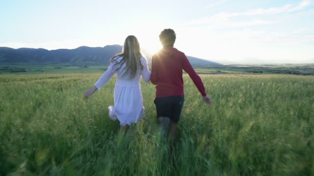 vidéos et rushes de ws ts sm rear view of young couple running through a field at sunset - couple d'adolescents