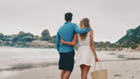 bakifrån av ungt par som går på stranden - helgaktivitet bildbanksvideor och videomaterial från bakom kulisserna