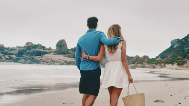 rear view of young couple walking at beach - weekend activities stock videos & royalty-free footage