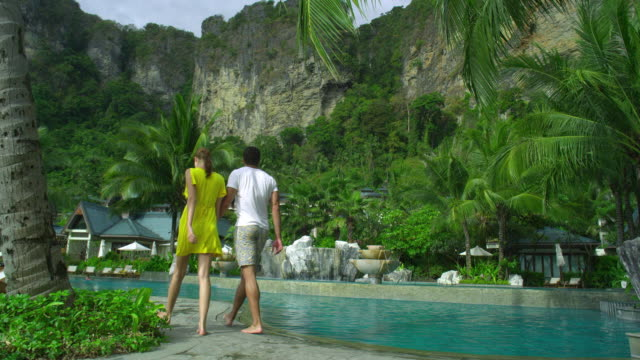 ws rear view of young couple walking on poolside of hotel resort in tropical surroundings, krabi, thailand - gemeinsam gehen stock-videos und b-roll-filmmaterial