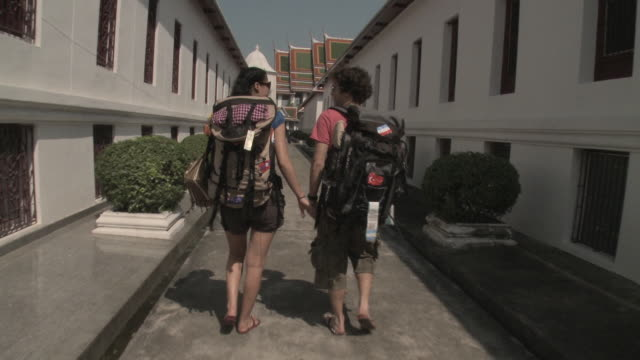 MS DS. Rear view of young couple with backpacks walking on narrow street, temple in background, Bangkok, Thailand