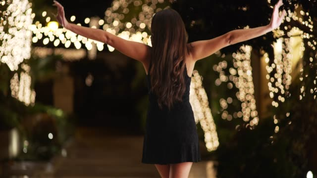 rear view of young latina female in sexy black dress dancing outside in evening - black dress stock videos & royalty-free footage